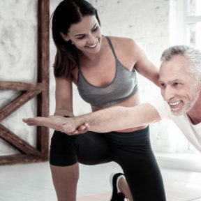Motivated and strong. Radiant elderly gentleman smiling cheerfully while exercising with his fitness coach and training at a gym.